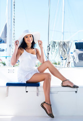 Young and sexy brunette woman in a white dress on a boat