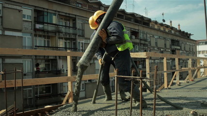 Workers with helmets on heads pulling hose for concreting slab