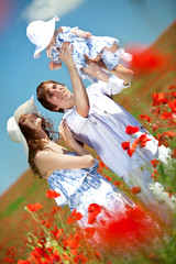 Happy young family in flowers field