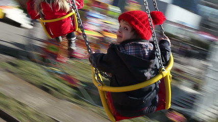 Adorable boy, going on a merry-go-round chain swing attraction