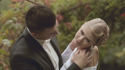 The groom gently kisses fiancee in the park