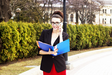 Business woman with folders and phone