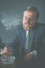 Handsome bearded businessman sitting smoking
