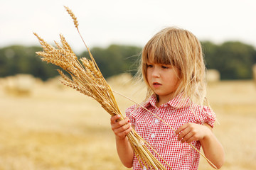 little girl on the field with wheat