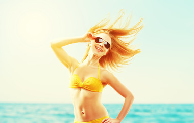 beautiful young woman with hair flying in the wind and sunglasse