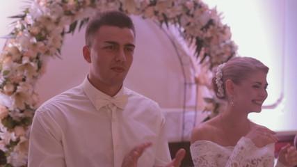 Newlyweds listening congratulations at a banquet