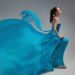 Beautiful woman in fluttering airy blue dress. Gray background.