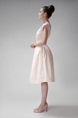 Beautiful woman in pink retro dress. Gray background.