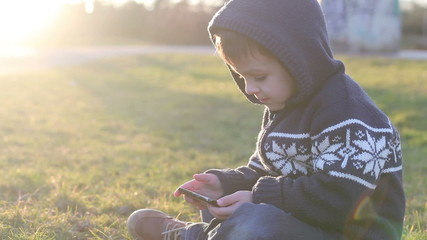 Cute boy, playing with phone on sunset, outdoor