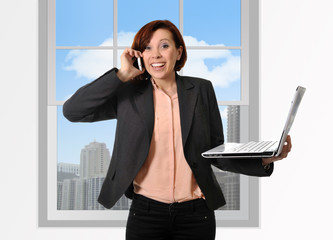 Happy business woman working on mobile cell phone and computer