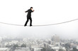 Businessman balancing and walking on the rope with urban scene