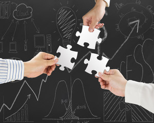 Group of business people assembling blank white jigsaw puzzles