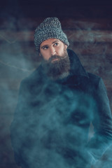 Handsome Man in Winter Outfit Behind a Smoke