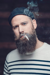 Serious Man with Long Goatee Smoking a Cigarette