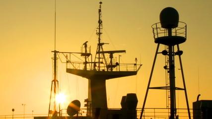 sun at dawn illuminates the ship masts and superstructure