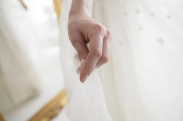 Hand holding a wedding dress