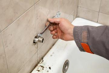Plumber works in a bathroom , fixing water pipe
