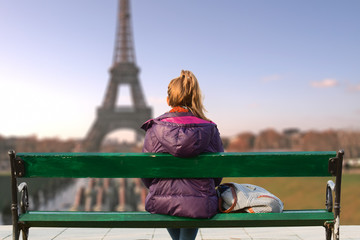 Lonesome girl watching at Paris city scape at sunset/sunrise.