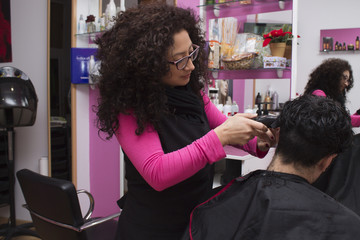 hairdresser cutting hair boy