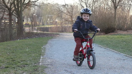Cute little boy riding a bike on a sunny afternoon