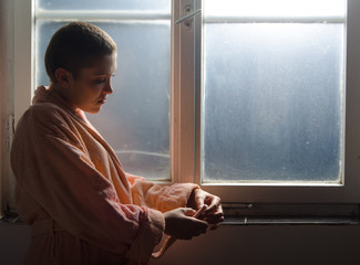 Young female cancer patient standing in front of hospital window