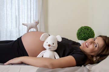 Close up view of a expecting pregnant woman with a stuffed toy.