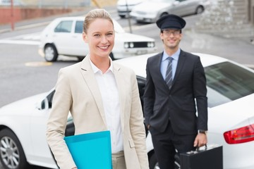 Businesswoman and her chauffeur smiling at camera