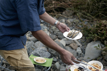 Man holding a plate of grilled fish at a picnic.
