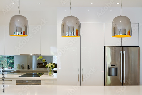 Contemporary pendant lights hanging over kitchen island - 79550425