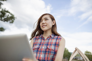 Young woman with a digital tablet in the park.