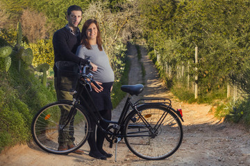 Close up view of a expecting happy couple on a bicycle.