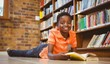 Cute boy reading book in library - 79551618