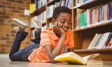 Cute boy reading book in library - 79551635