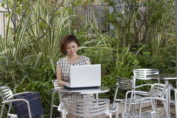 A woman seated using a laptop in a garden cafe in Namba Park.