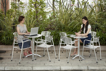 Two women seated in a garden cafe in Namba Park, one using a laptop, the other holding a cell phone.