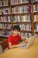 Portrait of boy using laptop in library