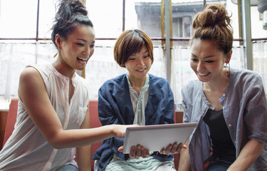 Three women looking at a digital tablet, sitting indoors.