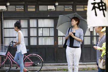 Woman standing outdoors, holding an umbrella.
