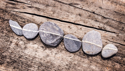 Lign of stones on a wooden background