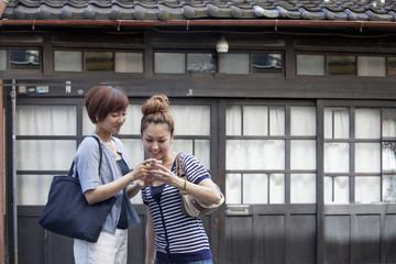 Two women standing outdoors, looking at cellphone.