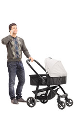Young father talking on phone and pushing a baby stroller