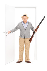 Angry senior holding a shotgun and walking through a door