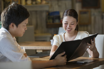 Woman and man sitting at a table in a cafe, looking at the menu, smiling.