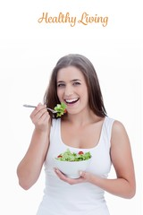Healthy living against smiling young woman eating a salad