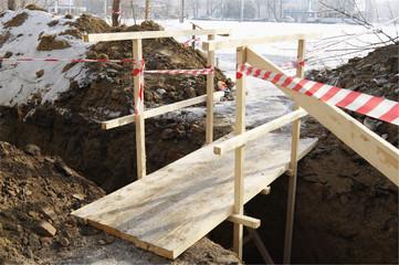 Wooden bridge over dug trench.