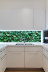 Residential contemporary kitchen sink with low window showing a