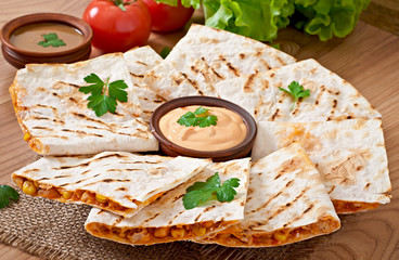 Mexican Quesadilla sliced with vegetables and sauces on the tabl