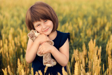 Girl with teddy bear in a field