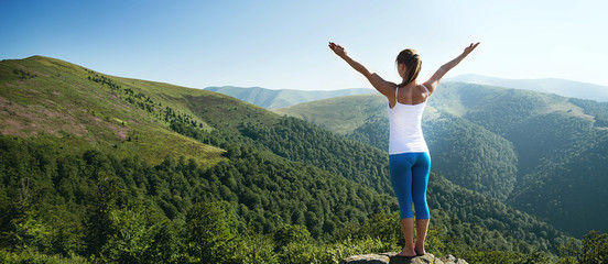 Young woman meditate on the top of mountain