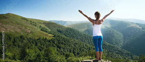 Leinwanddruck Bild Young woman meditate on the top of mountain